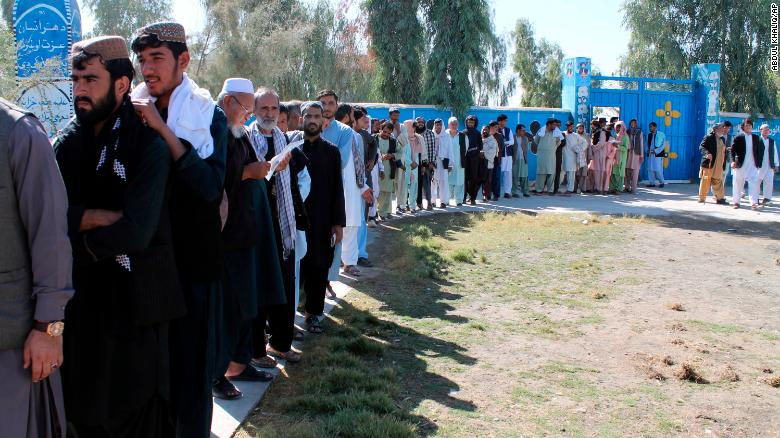 Afghan men line up to cast votes Saturday in Helmand province.