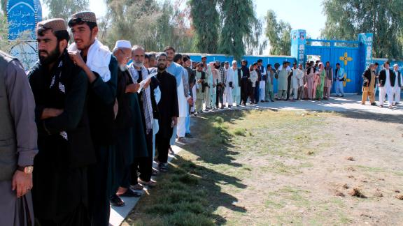 Afghan men line up to cast their votes, outside a polling station during the Parliamentary election in Helmand province, south of Afghanistan, Saturday, October 20, 2018.  Tens of thousands of Afghan forces fanned out across the country to provide security, as voting began Saturday in the elections that followed a campaign marred by relentless violence.