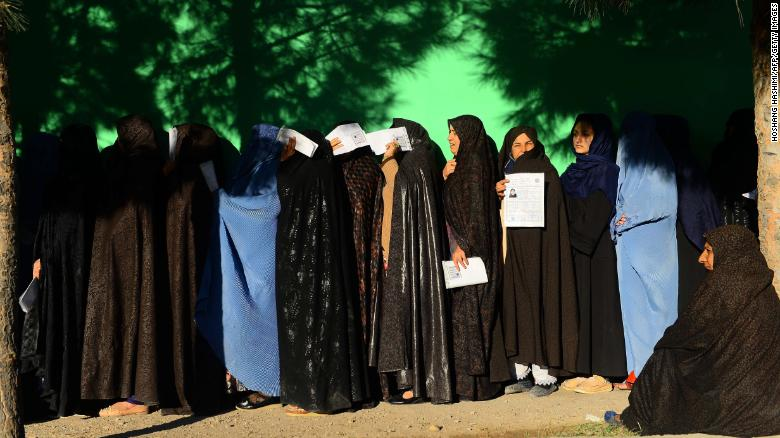 Afghan women wait in line to vote Saturday at a polling center in Herat province.