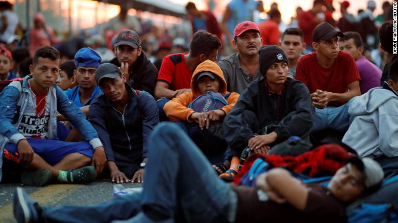 Honduran migrants wait for a gate on a bridge connecting Mexico and Guatemala in Ciudad Hidalgo, Mexico, to open.