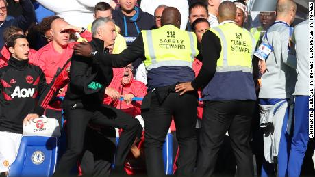 Stewards hold back Jose Mourinho as he clashes with the Chelsea backroom staff.