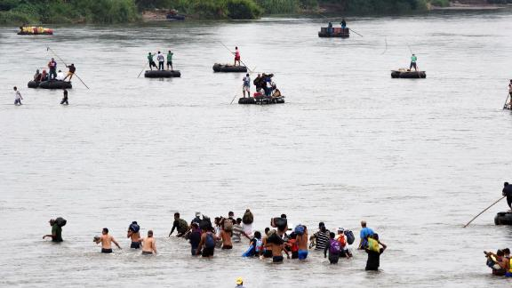 Honduran migrants from the caravan on Saturday cross the Suchiate River, a natural border between Guatemala and Mexico.
