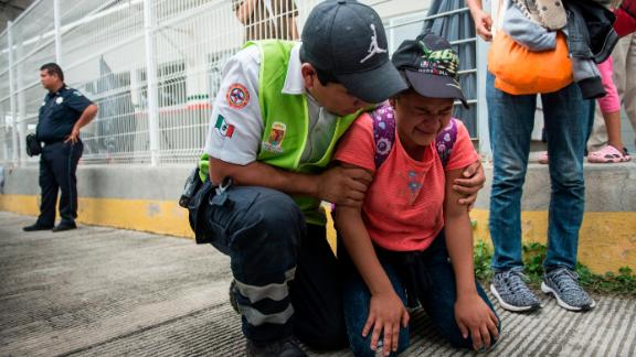 A migrant is comforted by a Mexican paramedic after her mother fainted while crossing the border between Guatemala and Mexico.