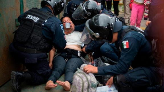 Mexican paramedics help a Honduran woman who fainted after crossing the border between Guatemala and Mexico on Saturday.