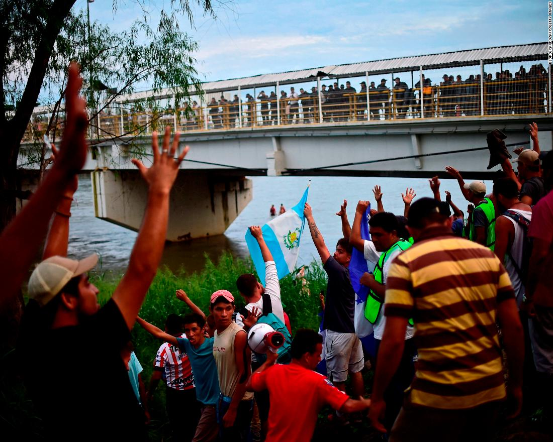 Honduran migrants from a caravan to the United States who have already reached Mexican soil cheer at the rest of the group still waiting to cross at the Guatemala-Mexico border bridge in Ciudad Hidalgo, Mexico, on Saturday, October 20.