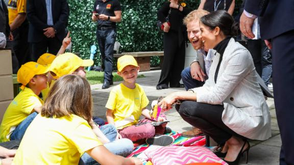 Britain's Prince Harry and Meghan, the Duchess of Sussex, talk with schoolchildren in Sydney on Sunday, October 21.