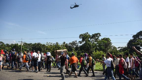 A Mexican Federal Police helicopter flies over migrants heading in a caravan to the United States, on the road linking Ciudad Hidalgo and Tapachula in Mexico.