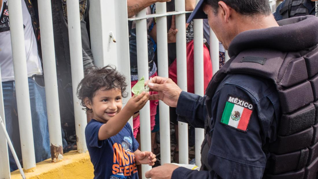 A young boy named Carlitos plays with a Mexican federal police officer as he waits with his mom on the bridge from Guatemala.