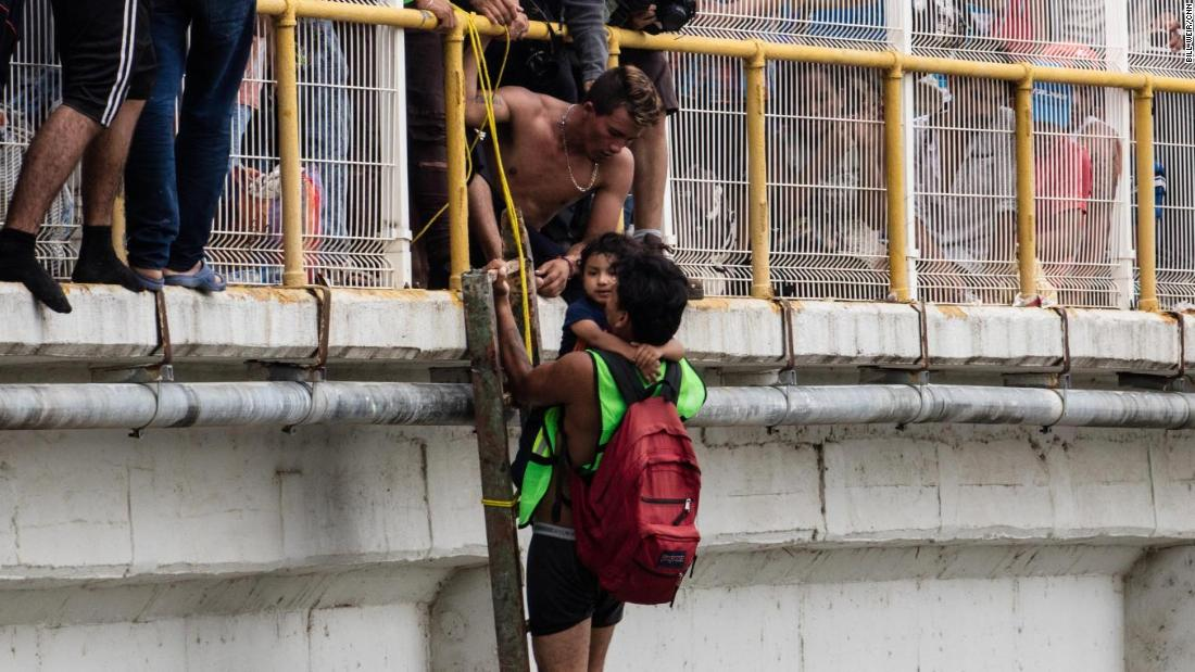 A man helps three-year-old Carlitos off the bridge and be lowered down to his mother, waiting on a raft on the river below.