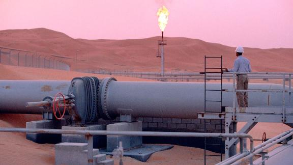 SHAYBAH, SAUDI ARABIA - MARCH 2003:  A worker stands at a pipeline, watching a flare stack at the Saudi Aramco oil field complex facilities at Shaybah in the Rub