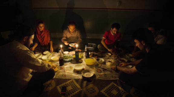 A family in Iraq sits by candlelight due to blackouts caused by the country's infrastructure problems.