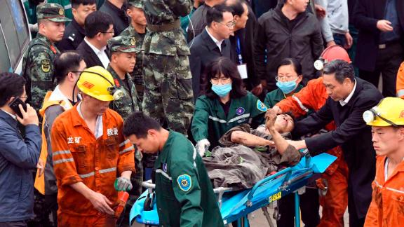 A worker is carried on a stretcher out of the Longyun coal mine in China's Shandong Province.