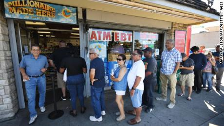 Customers buy Mega Millions tickets hours before the draw of the USD 1 billion jackpot, at the Bluebird Liquor store in Torrance, California on October 19, 2018.