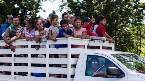 Migrants take a ride on a truck as they head north into Mexico.