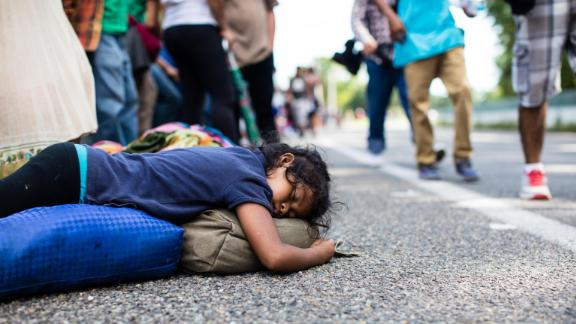 A girl sleeps on the side of the road as fellow migrants walk past.