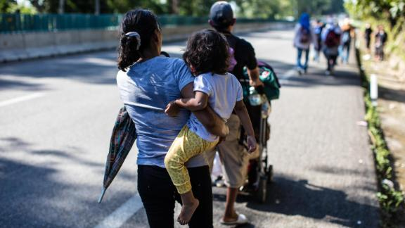 A child is carried as the crowds of migrants walk north from Tapachula.