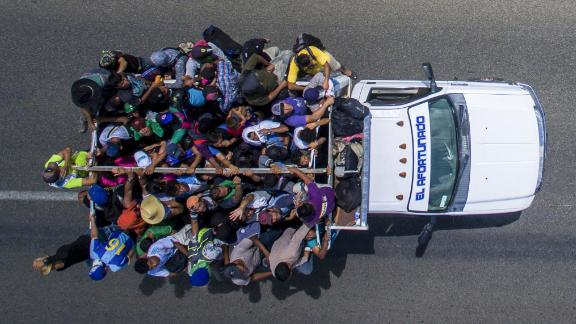 Migrants ride on the back of a truck heading to the US border from the outskirts of Tapachula, Mexico, on Monday, October 22. The majority of migrants made their way on foot. But some also flagged down cars and trucks passing by and piled onto any vehicle that would take them.