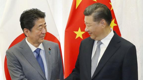 Japan's Prime Minister Shinzo Abe (L) shakes hands with China's President Xi Jinping (R) prior to their bilateral meeting in Vladivostok on September 12, 2018, on the sidelines of the Eastern Economic Forum hosted by Russia. (Photo by JIJI PRESS / Japan Pool via Jiji Press / AFP) / Japan OUT        (Photo credit should read JIJI PRESS/AFP/Getty Images)