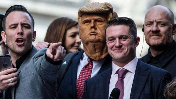 Far-right figurehead Tommy Robinson (2nd R), stands beside a man in a Donald Trump mask as he addresses supporters outside the Old Bailey on October 23.