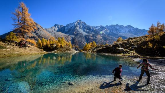 """Arolla, Switzerland: In mid-October in Arolla, western Switzerland, visitors throw stones in the """"Blue Lake."""" Algae and glacial clays colors the water this vivid blue."""