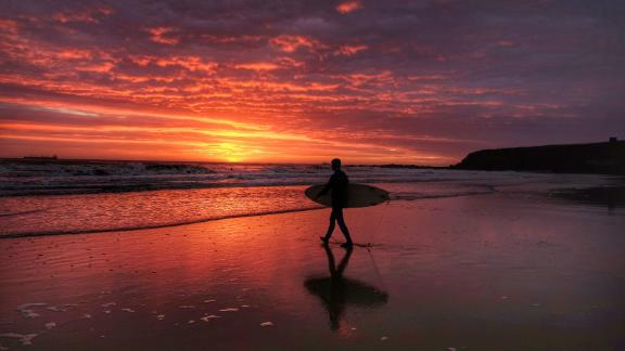 \North Tyneside, United Kingdom: A surfer heads toward the North Sea at sunrise in North Tyneside in northern England.