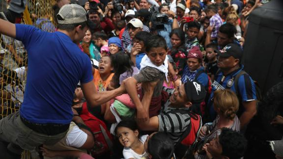 CIUDAD TECUN UMAN, GUATEMALA - OCTOBER 19:  Children in the migrant caravan are lifted over a gate at the Guatemala-Mexico border on October 19, 2018 in Ciudad Tecun Uman, Guatemala. The caravan of thousands of immigrants, most from Honduras, pushed past Guatemalan police before clashing with Mexican riot police.  (Photo by John Moore/Getty Images)