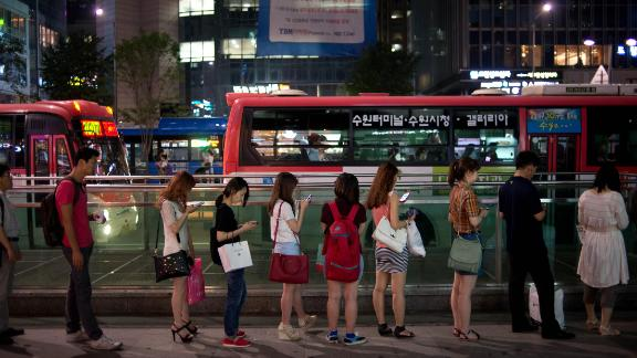 People wait for a bus on a street in the Gangnam district of Seoul on July 5, 2013. One of Asia