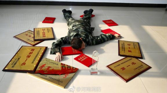 "A Henan Fire Department employee lies among the awards he has won for his work, the government body's response to the ""Flaunt your wealth"" campaign on Chinese social media."