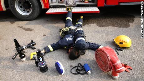 A Henan Fire Department firefighter lies among the tools he uses in his everyday job.