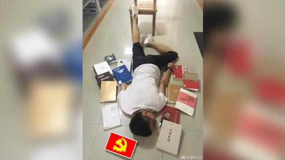 A student at Hainan University lies among his text books, including works about Karl Marx, Mao Zedong and Deng Xiaoping