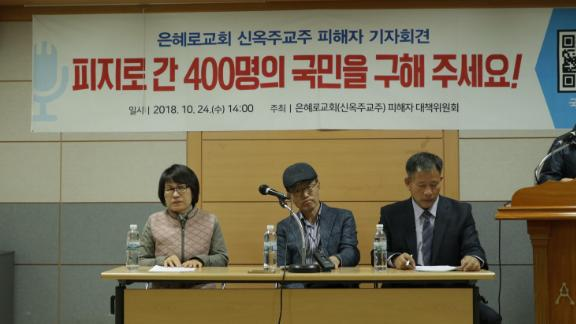"From left to right: Lee Soon-deok, Park Chan-moon and Lee Yoon-jae, former members of the Grace Road Church, speak at a news conference Wednesday. The banner above them reads ""Please rescue 400 South Koreans in Fiji!"""