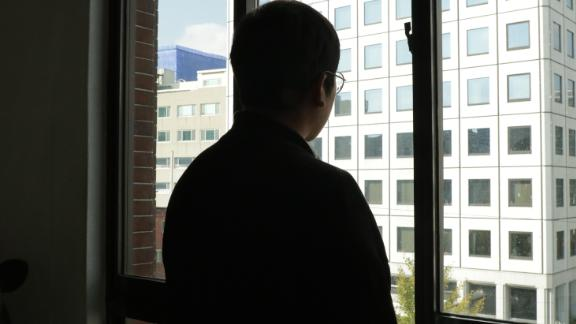 A man surnamed Hwang, a former Grace Road Church member, is seen looking out a window after speaking with CNN. CNN has agreed not to reveal his full identity due to fear of reprisals.