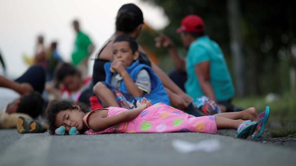 Families rest on a roadside between Mapastepec and Huixtla, Mexico, while traveling with thousands of migrants from Central America in a caravan en route to the United States, on Wednesday, October 24.