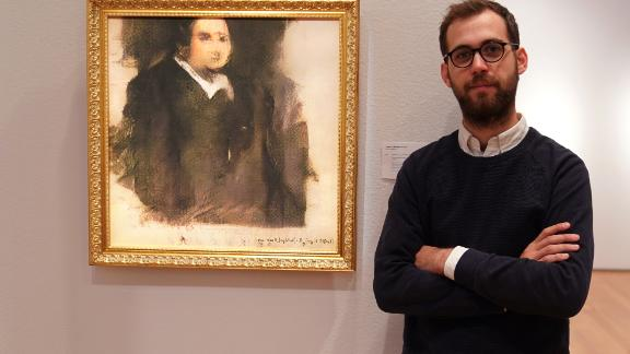 """Pierre Fautrel, co-founder of a group that produces art using AI, stands next to """"Portrait of Edmond de Belamy,"""" the first work produced by a machine to be sold at auction."""