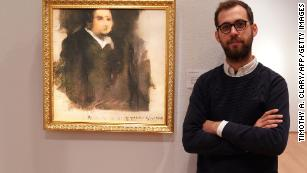 "Pierre Fautrel, co-founder of a group that produces art using AI, stands next to ""Portrait of Edmond de Belamy,"" the first work produced by a machine to be sold at auction."
