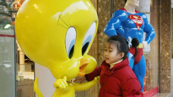 A young Chinese girl plays on a 'Tweety Bird' statue outside a newly opened Warner Brothers store on the Nanjing Road shopping street in Shanghai, 09 February 2006.
