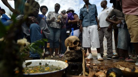 Voodoo devotees take part during ceremonies honoring the Haitian voodoo spirit of Baron Samdi and Gede on the Day of the Dead in the National Cemetery, in Port-au-Prince, Haiti, on November 2, 2017. Voodoo believers and devotees offer candles, alcohol and food. The Day of the Dead is celebrated on the first two days of November during All Saints and All Souls Day. / AFP PHOTO / HECTOR RETAMAL        (Photo credit should read HECTOR RETAMAL/AFP/Getty Images)
