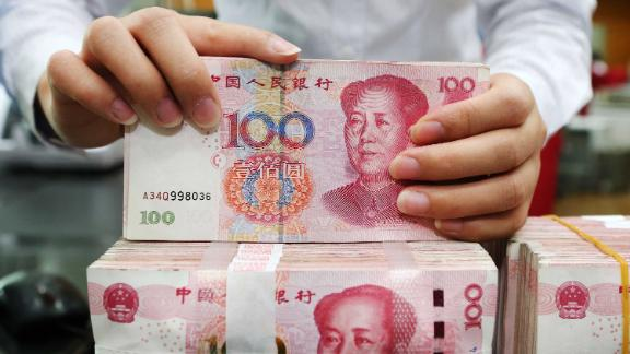 """An employee counts 100-yuan notes at a bank in Nantong in China's eastern Jiangsu province on July 23, 2018. - China on July 23 rejected accusations by US President Donald Trump that it was manipulating the yuan to give its exporters an edge, saying Washington appeared """"bent on provoking a trade war"""". (Photo by - / AFP) / China OUT        (Photo credit should read -/AFP/Getty Images)"""