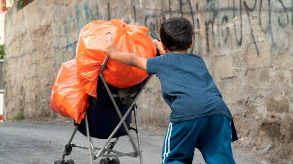 A boy pushes his trash up the road in Jabel Mukaber.