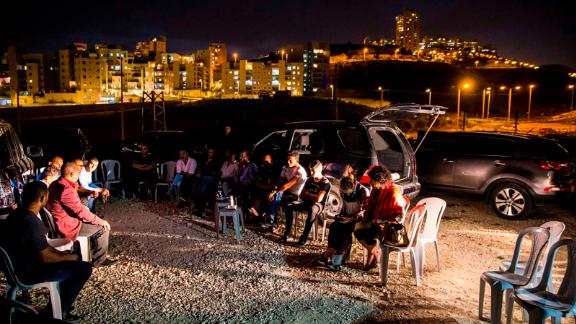 A group of local residents listens to Ramadan Dabash in Um Tuba, with the lights of Har Homa in the background.