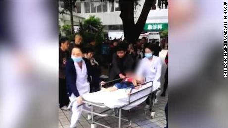 An image from state media shows children being rushed to hospital after a stabbing attack at a kindergarten in Chongqing. The child's face has been blurred.