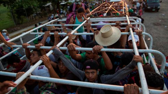 Migrants travel on a cattle truck, as a thousands-strong caravan of Central American migrants slowly makes its way toward the US border, between Pijijiapan and Arriaga, Mexico, on Friday, October 26.