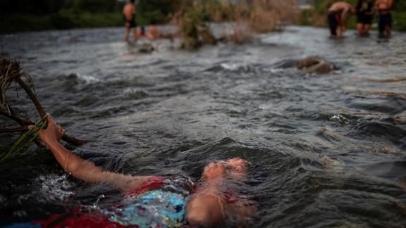 Jensi, a 14 year old migrant girl from Honduras, baths in a fresh water stream as she and others, part of caravan of thousands from Central America en route to the United States, take rest in Pijijiapan, Mexico on October 25.