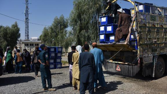 Afghan election employees unload ballot boxes from a truck at a polling center Friday ahead of Saturday's legislative polls in Kandahar province.
