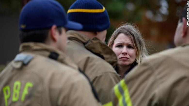 An unidentified woman asks for a status update from Pittsburgh City firefighters a block away from the site of a mass shooting at the Tree of Life Synagogue on October 27, 2018 in Pittsburgh.
