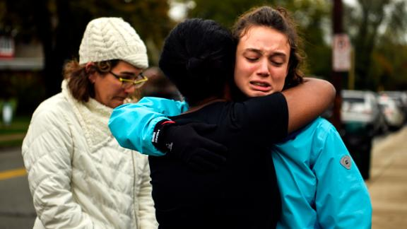 From left, Kate Rothstein looks on as Tammy Hepps hugs Simone Rothstein, 16, after multiple people were shot at The Tree of Life Congregation synagogue