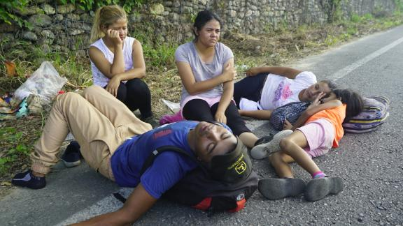 Iris, who did not want to give her last name, sits holding her head as her family collapses in exhaustion on the road to Arriaga, Mexico.