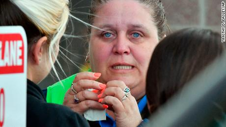 A Kroger employee wipes away tears following Wednesday's shooting in Jeffersontown, Kentucky, that left two people dead.