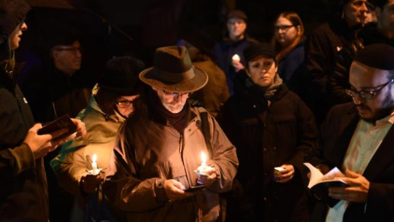 People hold candles outside the Tree of Life Synagogue after a shooting there left 11 people dead in the Squirrel Hill neighborhood of Pittsburgh on October 27, 2018. - A heavily armed gunman opened fire during a baby-naming ceremony at a synagogue in the US city of Pittsburgh on October 27, killing 11 people and injuring six in the deadliest anti-Semitic attack in recent American history. (Photo by Brendan Smialowski / AFP)        (Photo credit should read BRENDAN SMIALOWSKI/AFP/Getty Images)