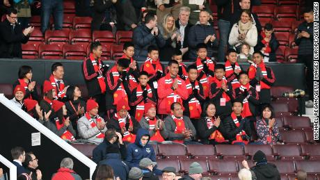 Players from the Moo Pa (Wild Boars) academy team are applauded by spectators at Old Trafford.